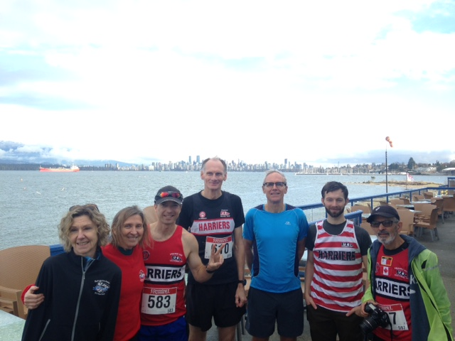 PIH's Leigh, Dawn, Johnny, Gary, Bill, Richard and Joseph posing after the 2018 LGRR 35th Gunner Shaw on the deck of the Jericho Sailing Centre with the downtown Vancouver skyline in the background across English Bay